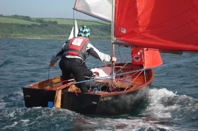 Black Mirror dinghy with helm steering with his knees and gybing the spinnaker