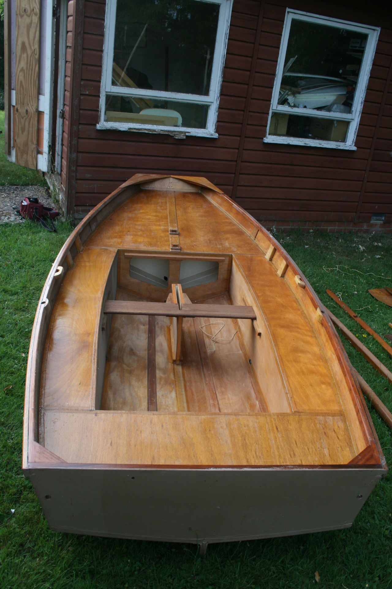 A wooden Mirror dinghy hull which has been completed and some varnish applied, but no fittings, on a lawn