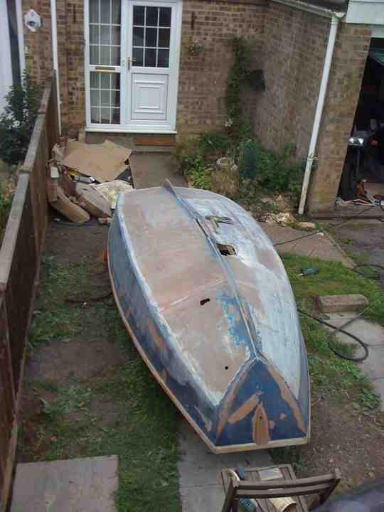 Mirror dinghy hull upside down with some paint removed and holes in hull