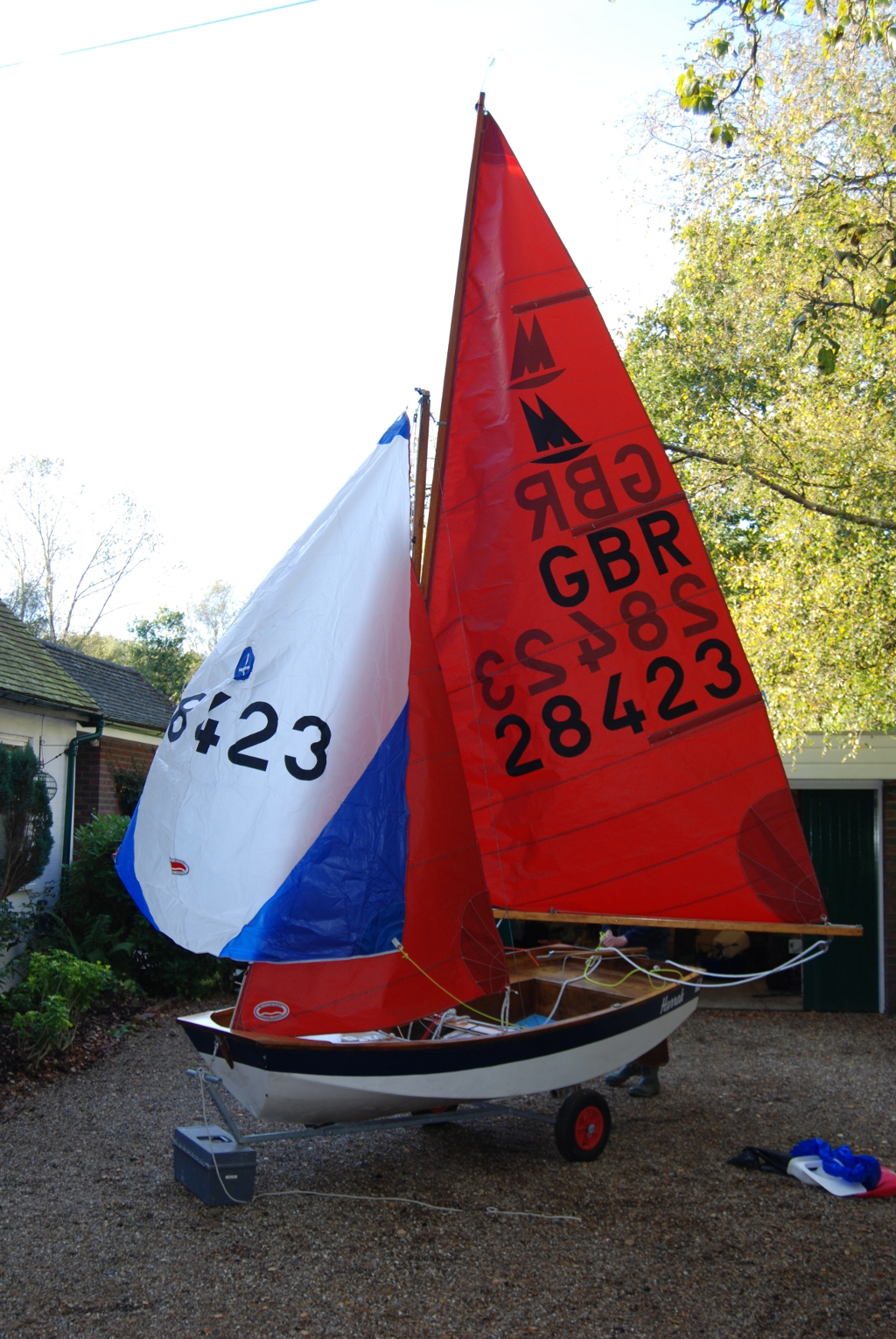 Mirror dinghy with main, jib and spinnaker hoised in driveway