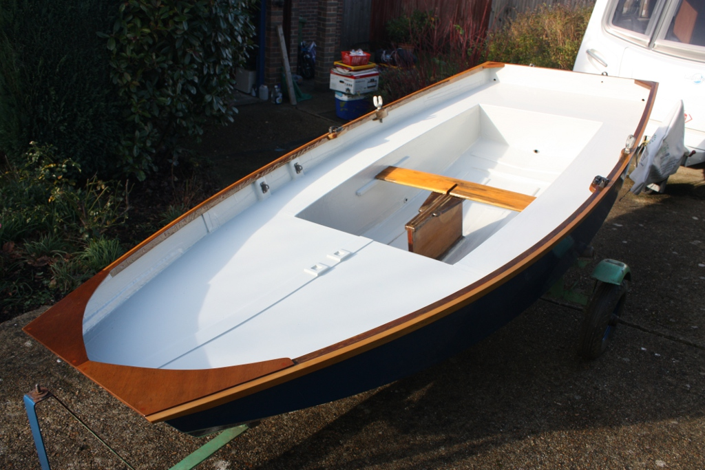 A blue Mirror dinghy painted white on the inside on a trolly