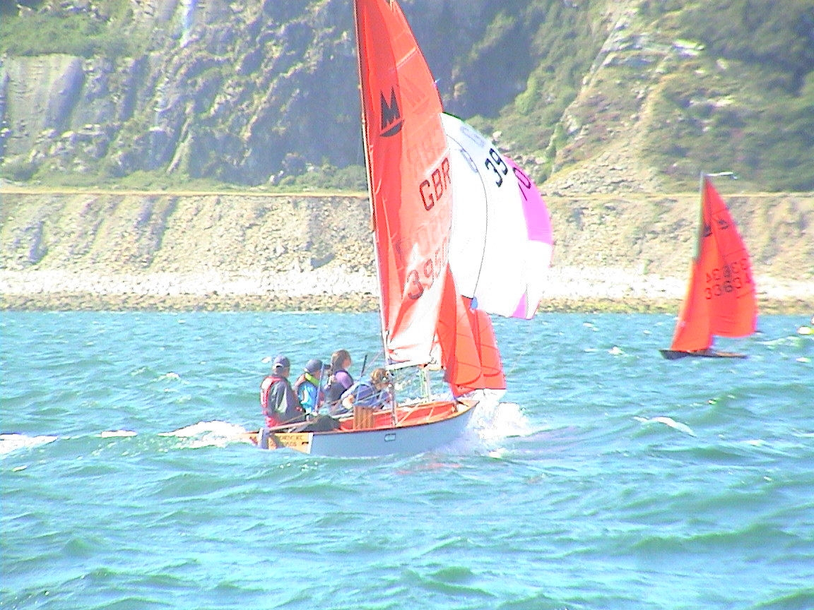 Mirror dinghies racing downwind on a blue sea