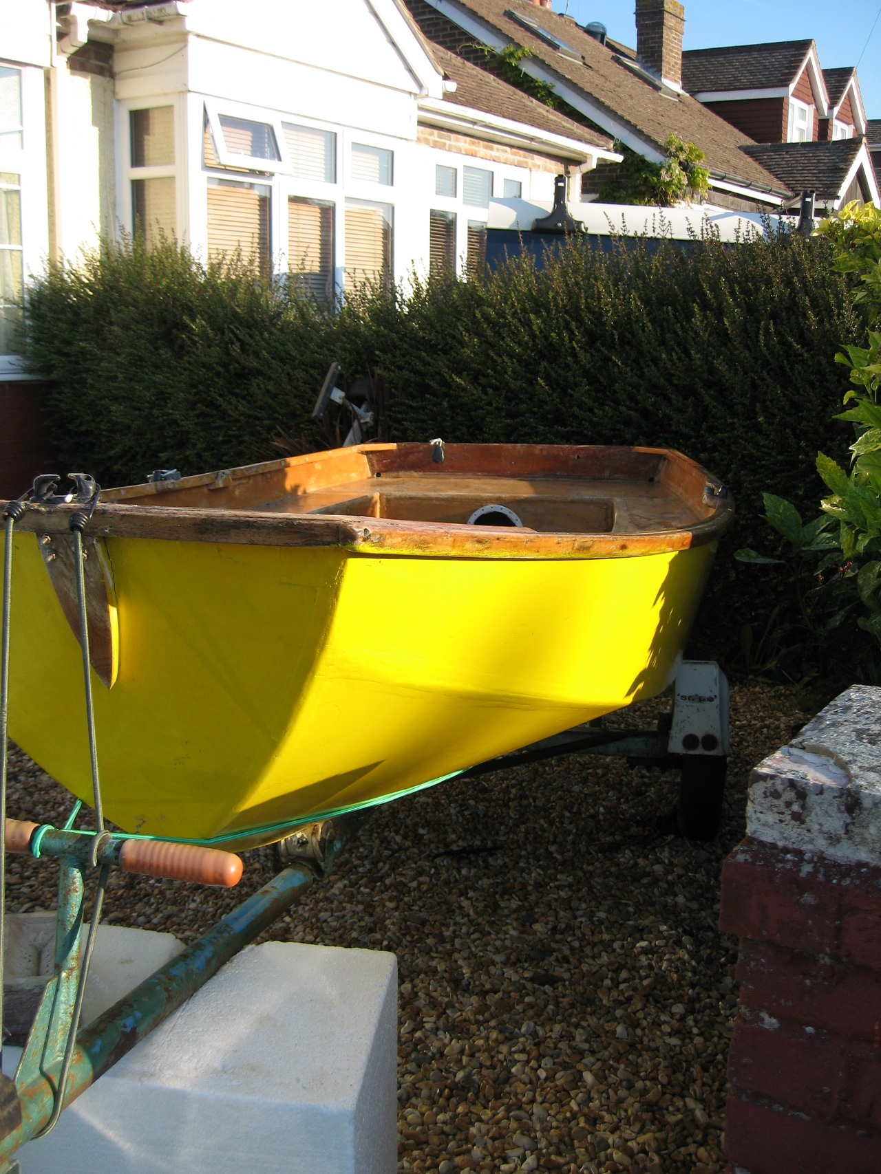 A yellow wooden Mirror dinghy on a road trailer on a drive