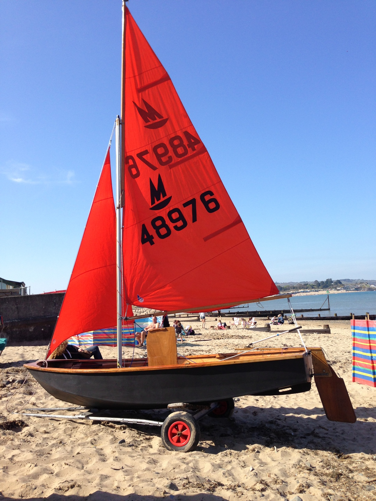 Mirror dinghy rigged up on a sandy beach with sails hoisted