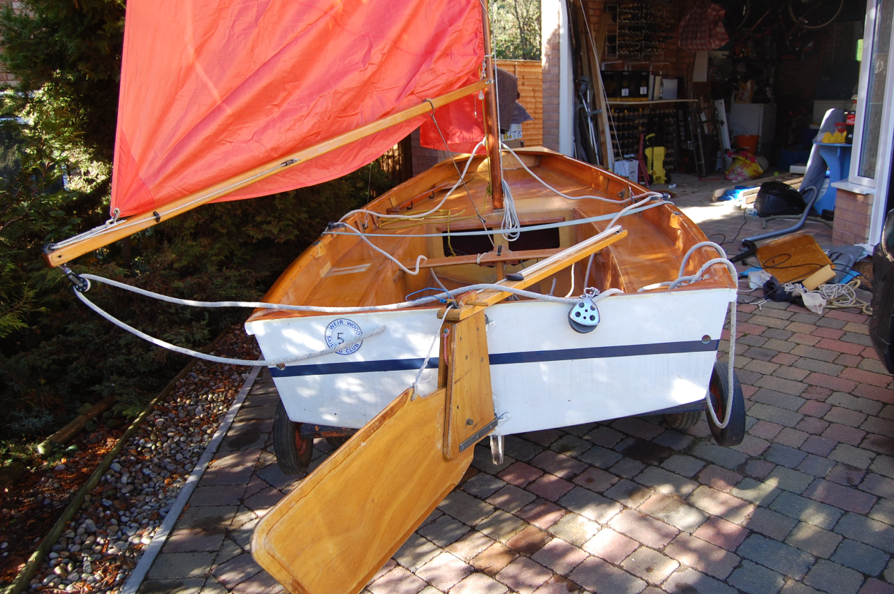 A Mirror dinghy rigged up on a drive outside a garage