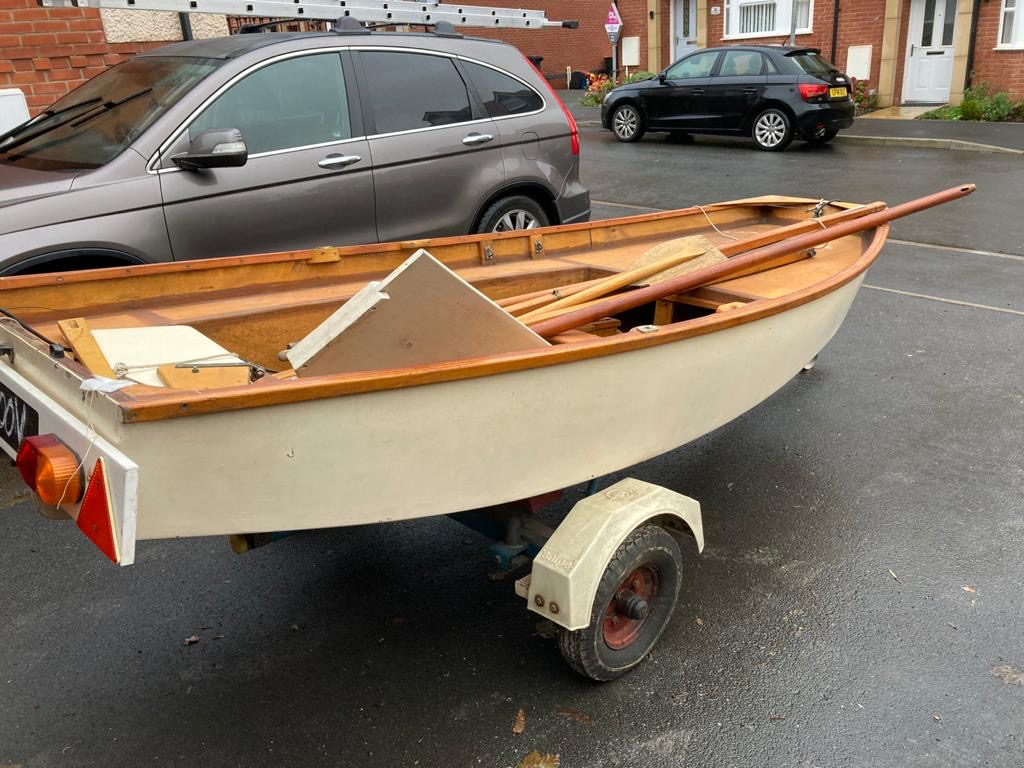 A white wooden Mirror dinghy with spars and oars lying inside the hull, on a road trailer on a driveway