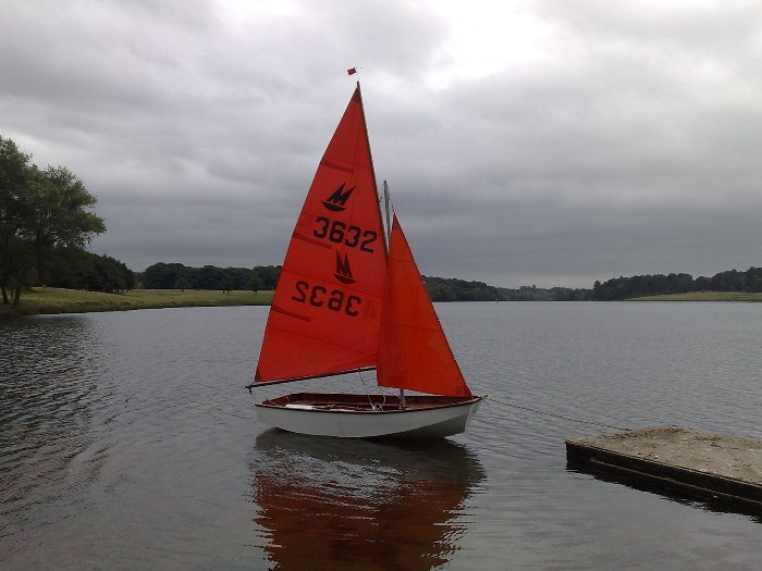 Mirror dinghy with sails hoisted tied to a pontoon on a lake