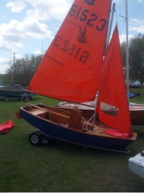Blue Mirror dinghy rigged with sails hoisted in grassed dinghy park