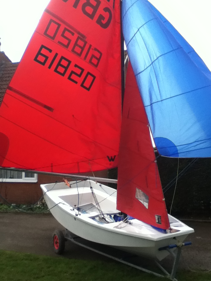 Mirror dinghy in a garden with mainsail, jib and spinnaker hoisted