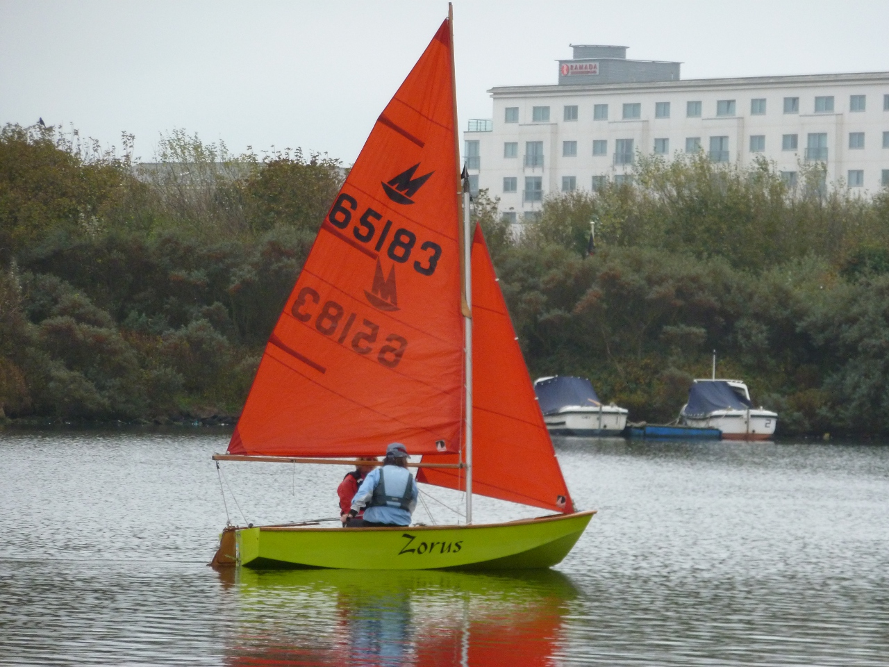 A lime green Mirror dinghy sailing on a lake in a light wind on a dull day