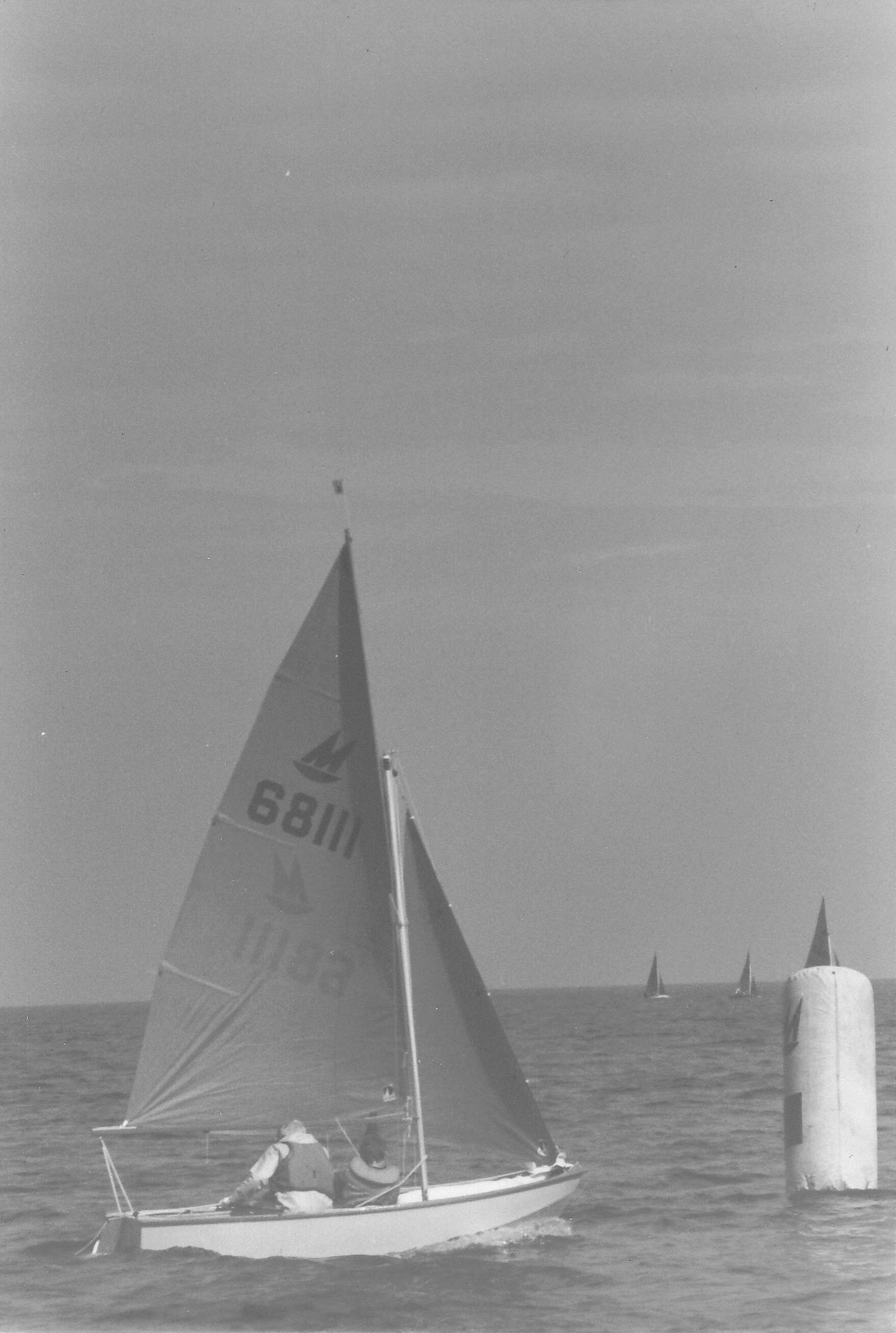 A wooden Mirror dinghy racing to windward with the windward mark nearby