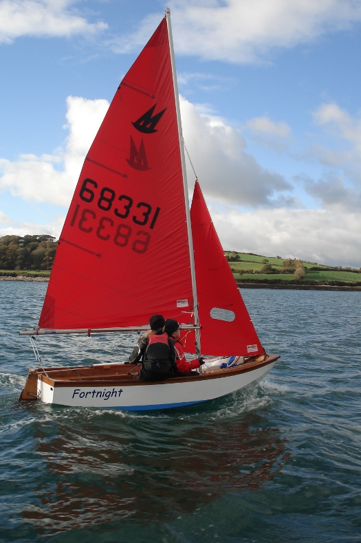 Mirror dinghy 68331 sailing upwind in a gentle/moderate breeze with blue sky and sunshine