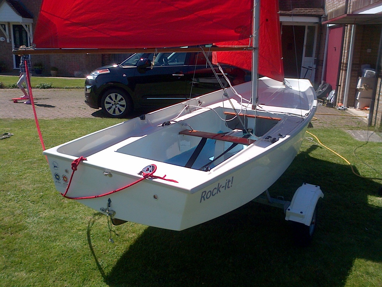 A Bell Ferranti GRP Mirror dinghy rigged up on a lawn