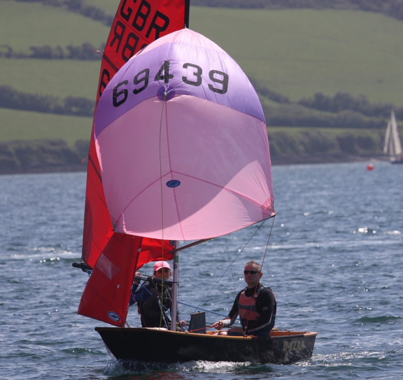 Black wooden Mirror dinghy 'B-Czar' running with pink and purple spinnaker on a sunny day
