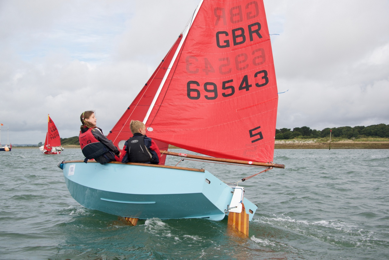A light blue Mirror dinghy being sailed to windward by two children well heeled over