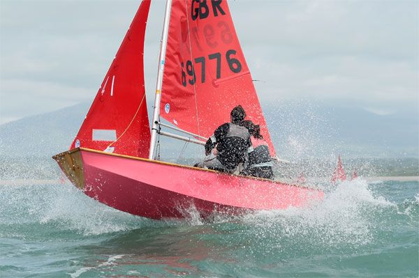 Pink wooden Mirror dinghy almost airborne in a big wave