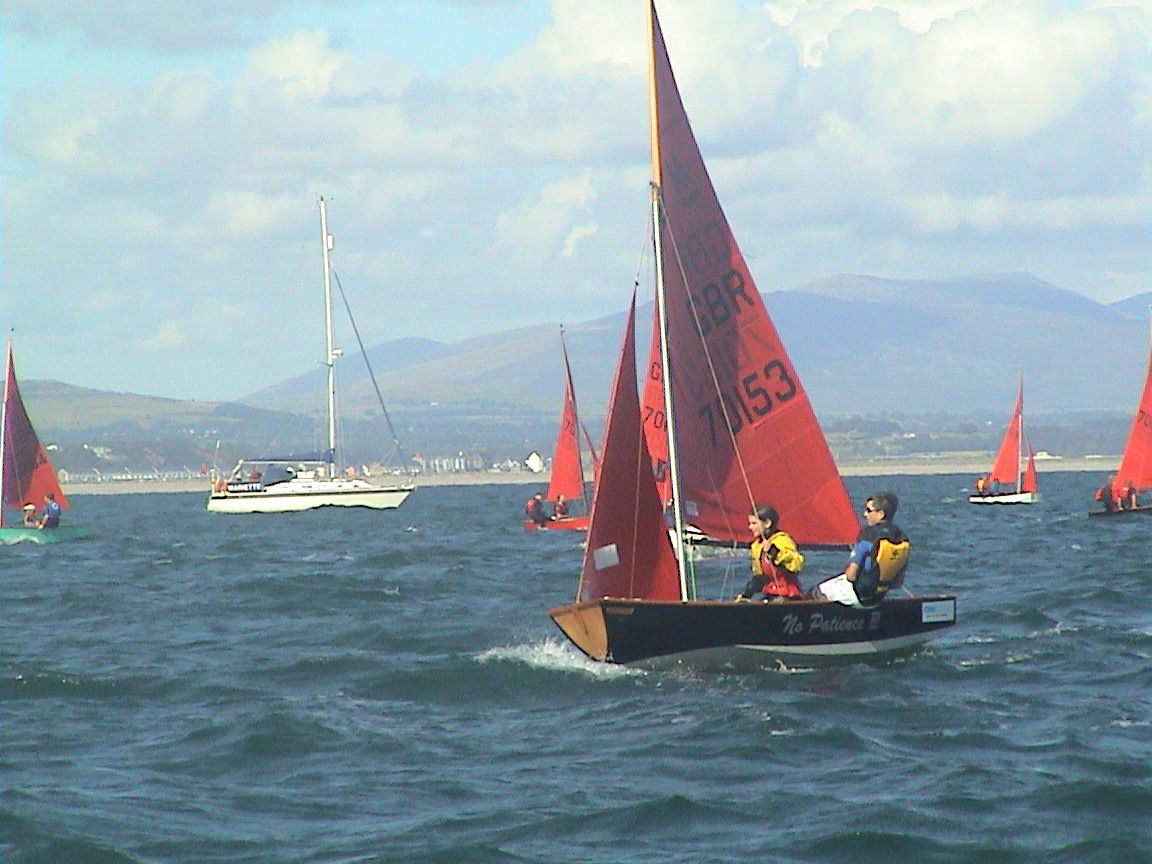 A black wooden Mirror dinghy racing to windward on port tack