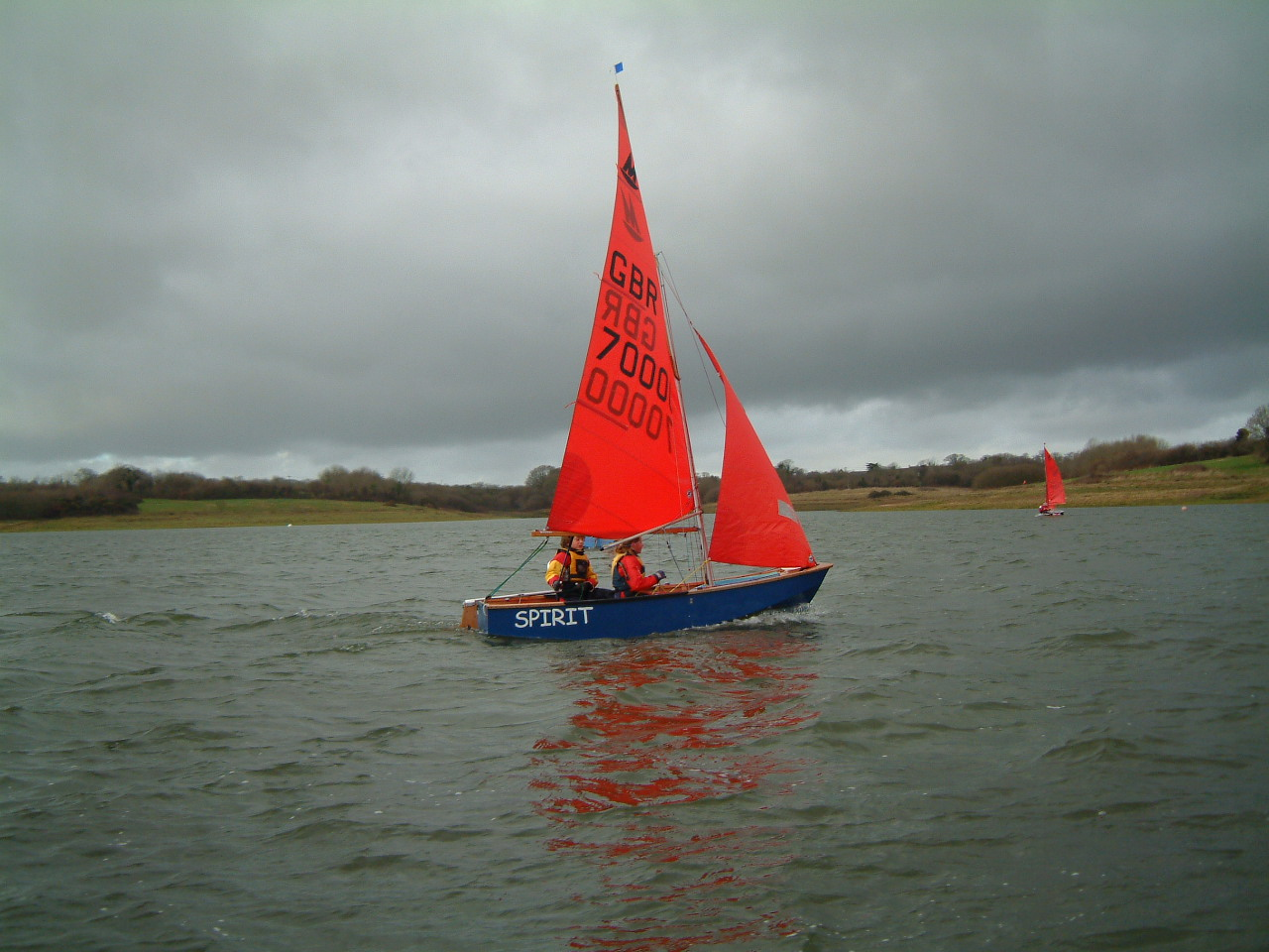 A blue wooden Mirror dinghy sailing on a lake on a dull and cold looking winter's day