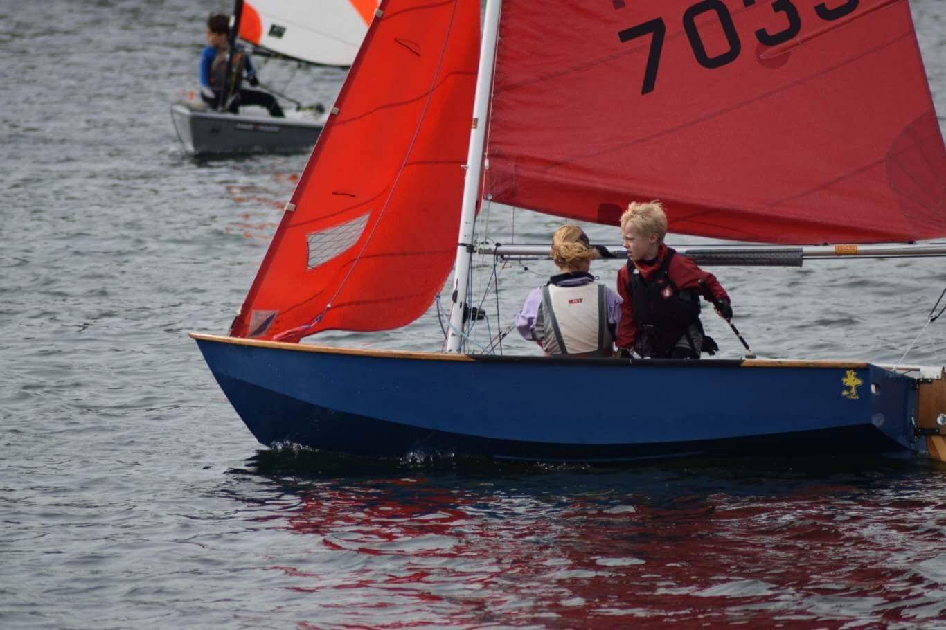 A blue wooden Mirror dinghy just being tacked very stylishly by a young boy
