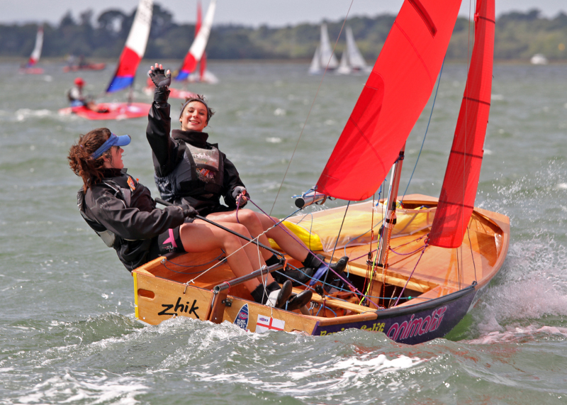 Beautiful wooden Mirror dinghy being sailed upwind by two girls