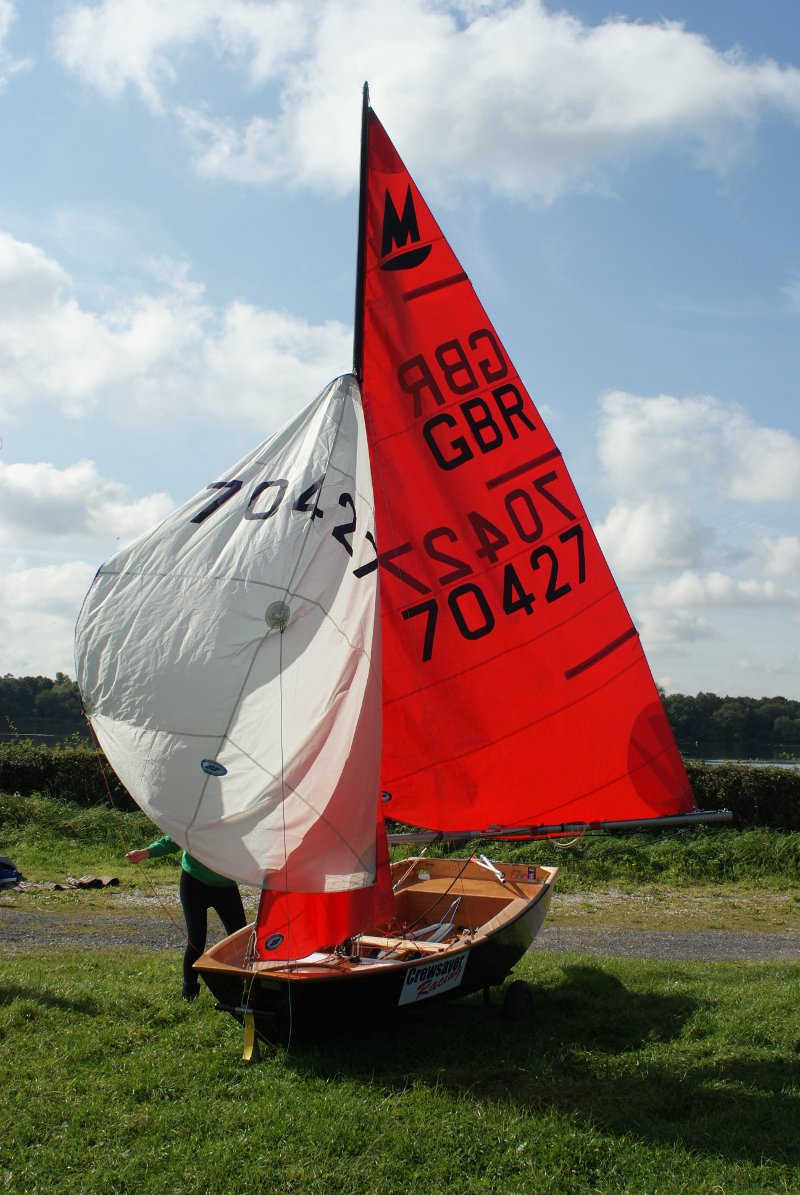 Black Mirror dinghy in a grassy dingy park with all sails hoised