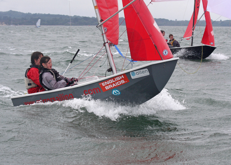 Grey GRP Mirror dinghy surfing on a grey day