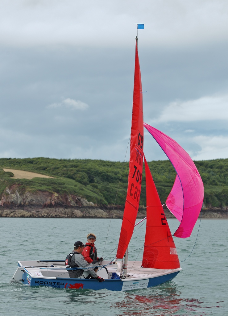 Blue and white GRP Mirror dinghy with pink spinnaker running downwind