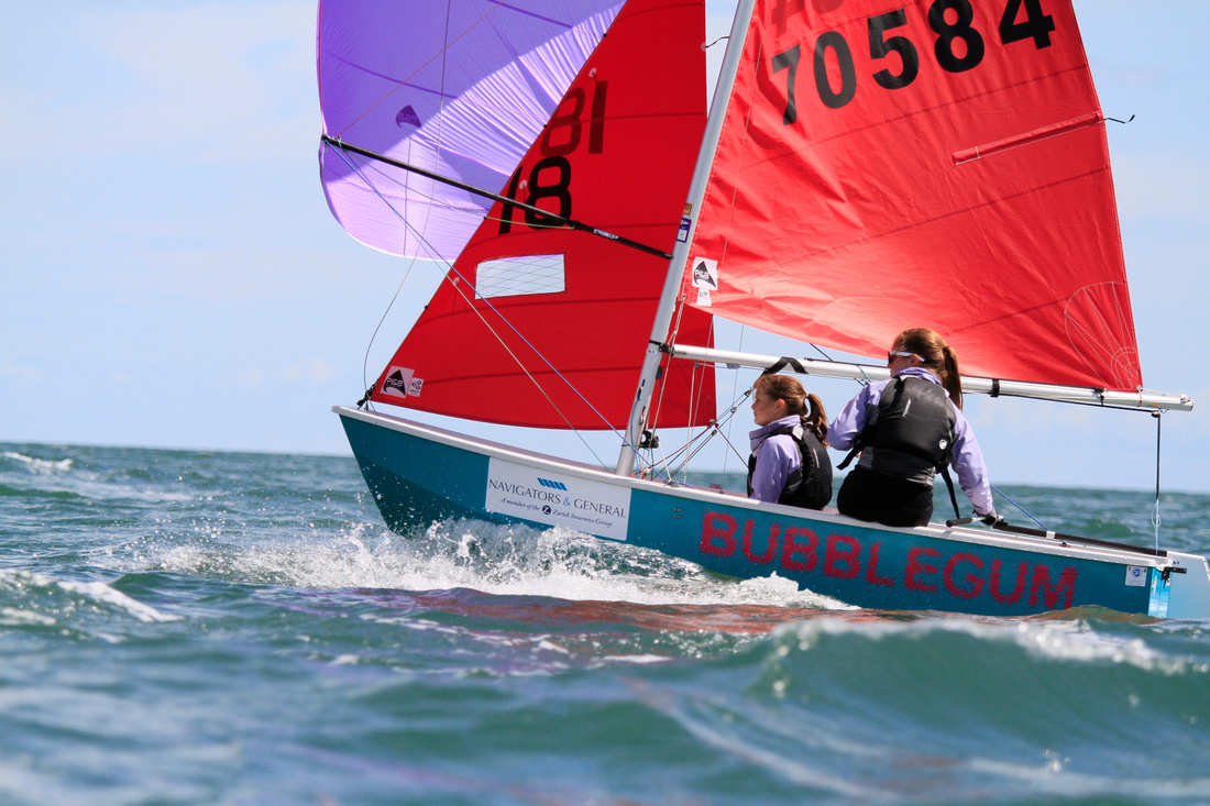 An aquamarine GRP Mirror racing with spinnaker up on a sunny day