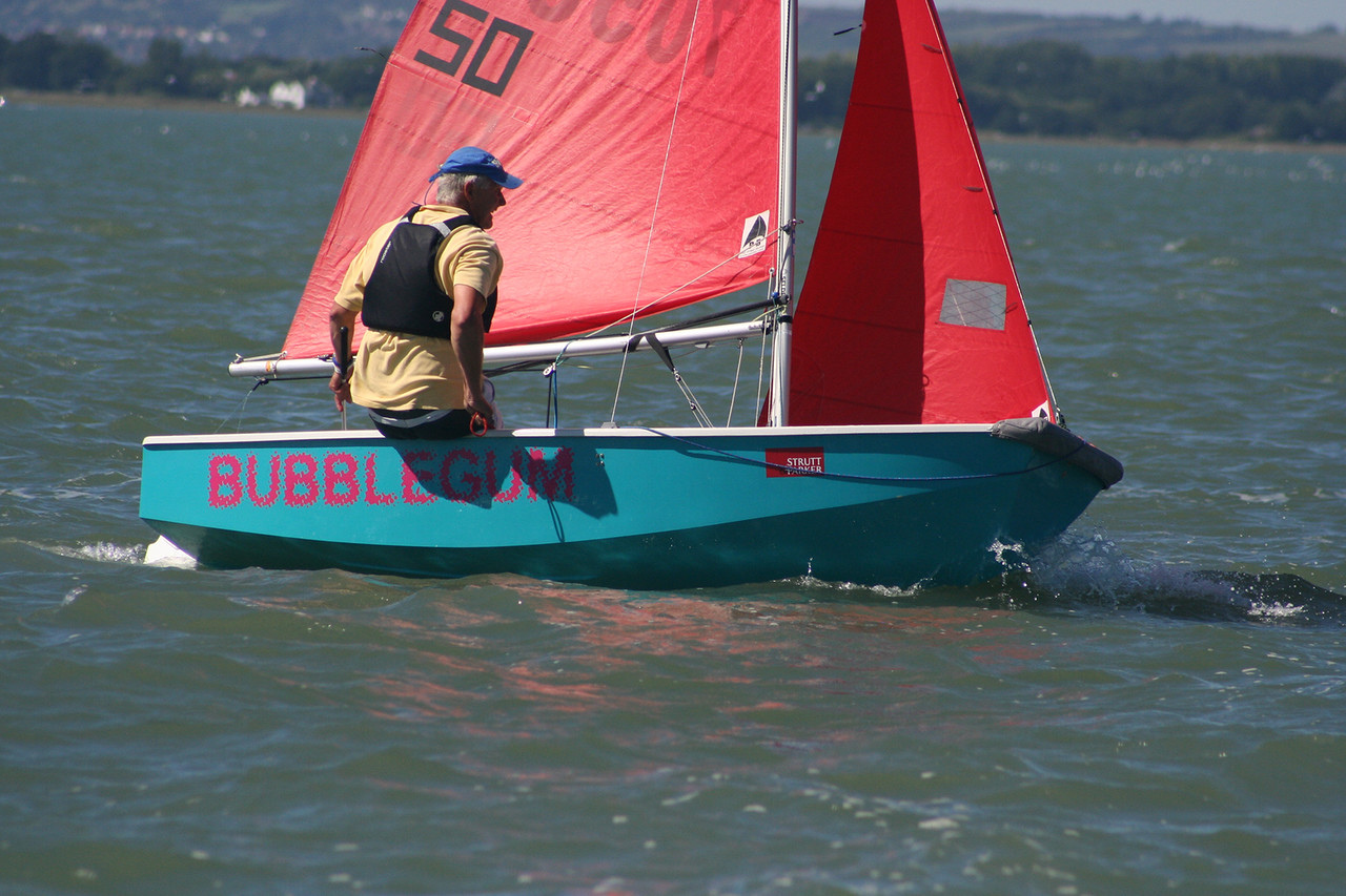 An aquamarine Mirror dinghy being race singlehanded