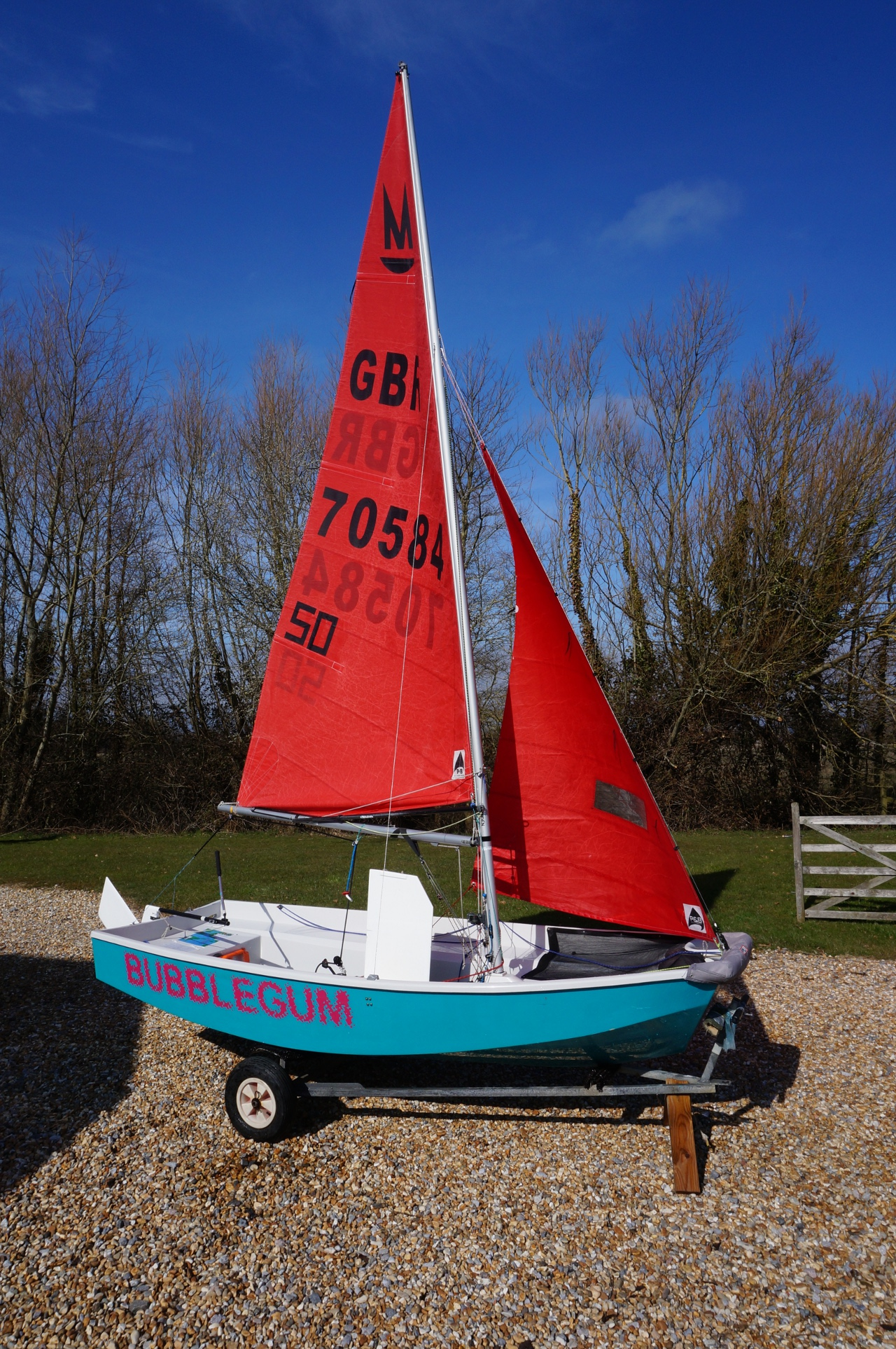 An aquamarine Mirror dinghy rigged up on a driveway