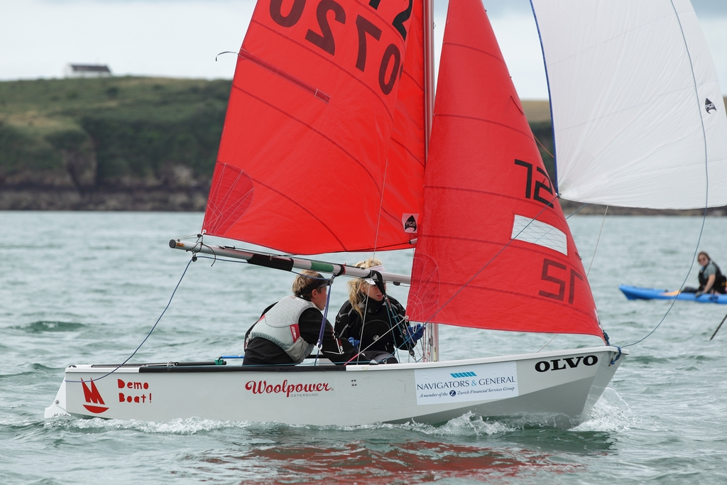 White GRP Mirror dinghy running downwind with white spinnaker set