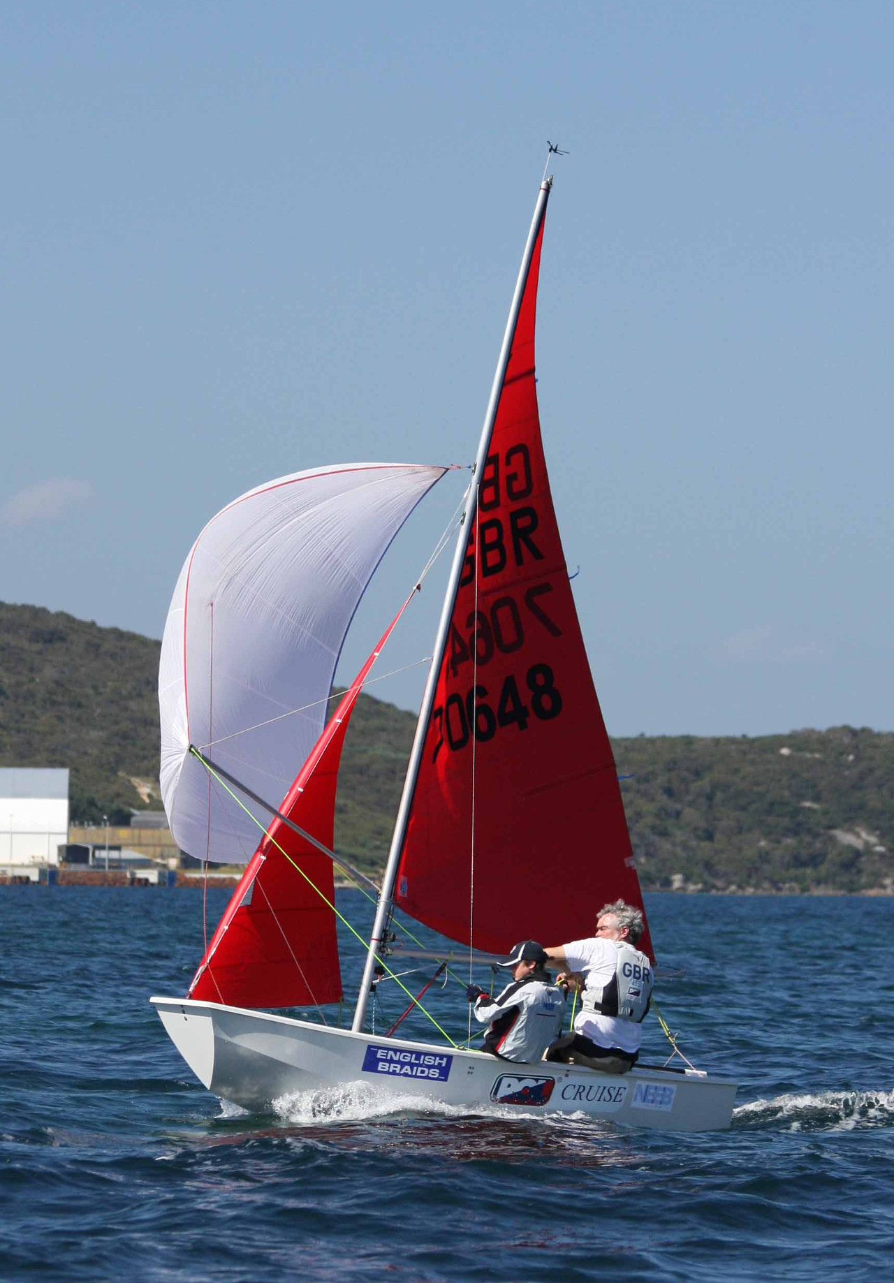 A white GRP Mirror dinghy sailing on a reach with spinnaker set