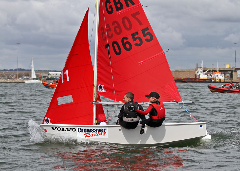 A white GRP Mirror dinghy after crossing the finishing line