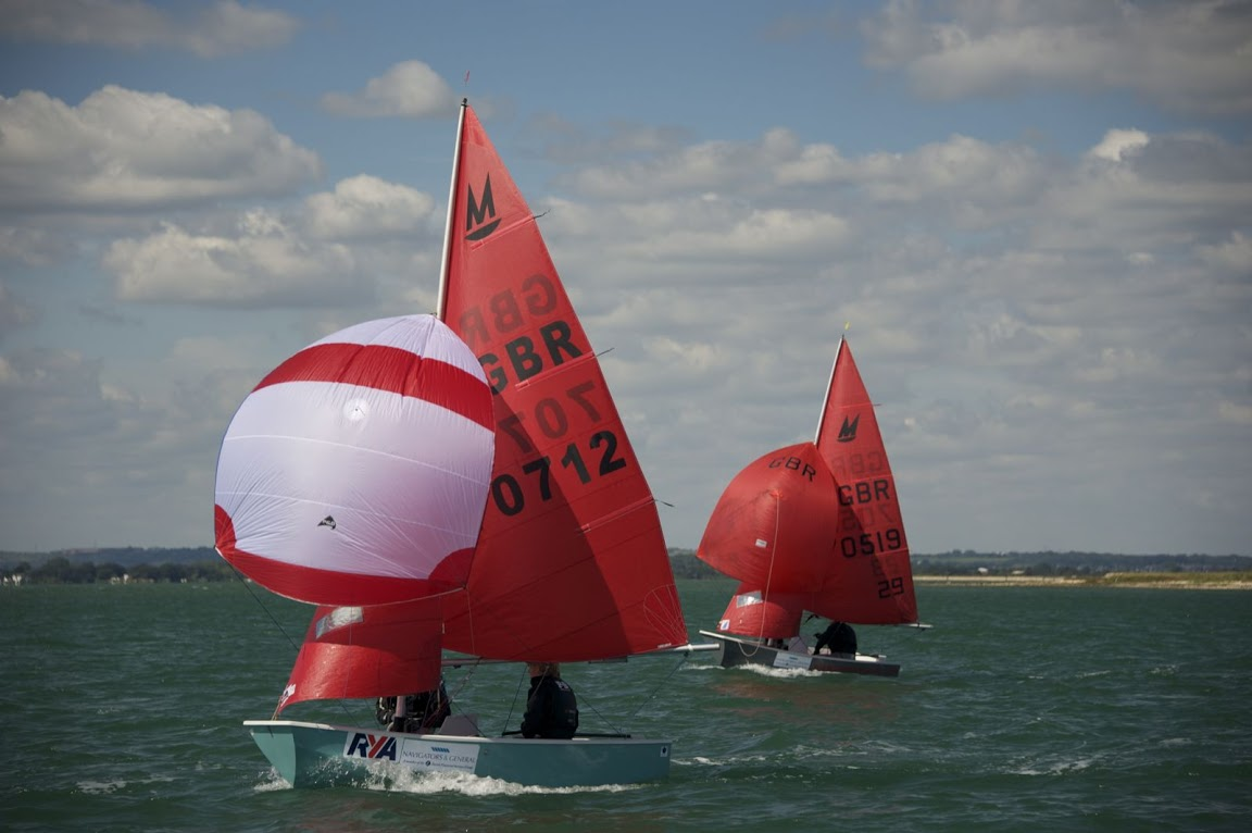 Blue-green GRP Mirror dinghy with white and red striped spinnaker
