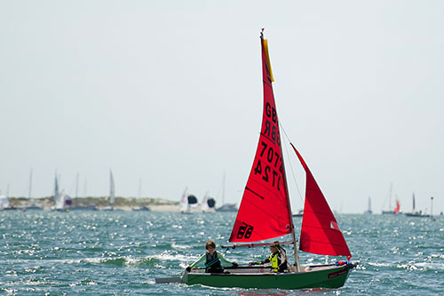 A green GRP Mirror dinghy being sailed in the distance with the rudder up