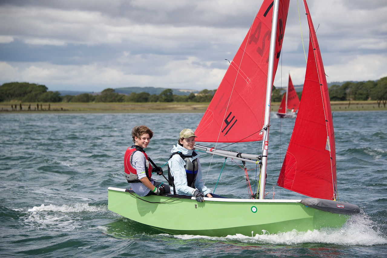 A green GRP Mirror dinghy being sailed to windward by a boy and a girl