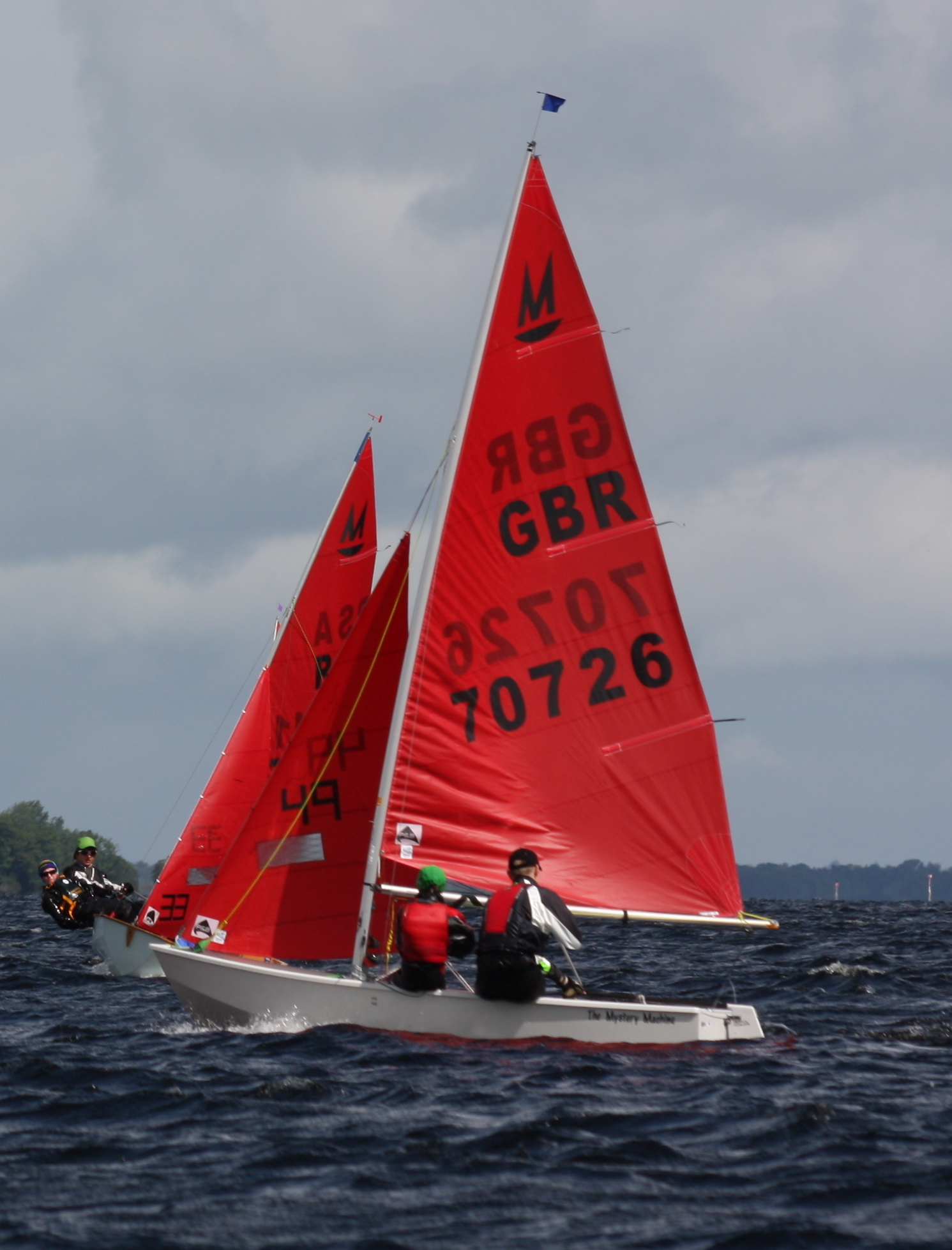 White Mirror dinghy on port about to tack to avoid a Mirror on starboard tack