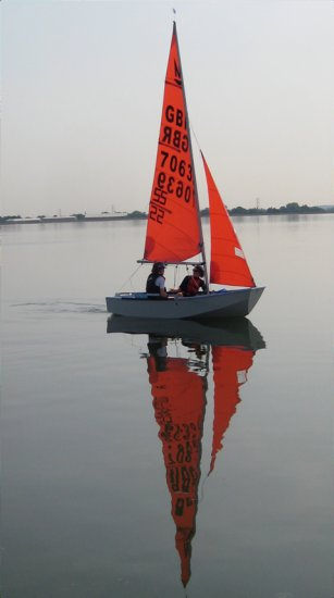 A Mirror dinghy sailing on a calm evening as the sun sets
