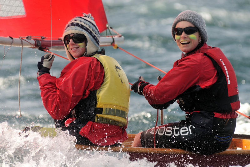 Two girls with green and yellow war paint on thier faces sailing a Mirror on a windy day