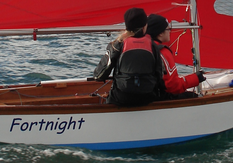 A Mirror dinghy sailing to windward with jib fairleads and cleats visible on the sidedeck