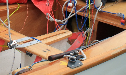 A plastic rowlock fitting on a white GRP/wood composite Mirror dinghy