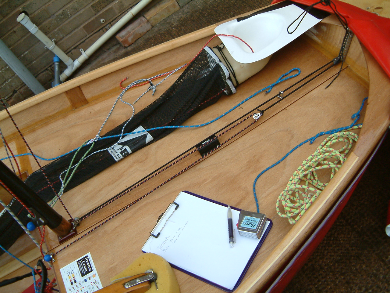 Foredeck of a Mirror dinghy with flyaway spinnaker pole downhaul elastic attached by free block