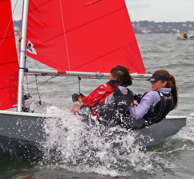 Two girls sailing a grey Mirror dinghy to windward in a chop