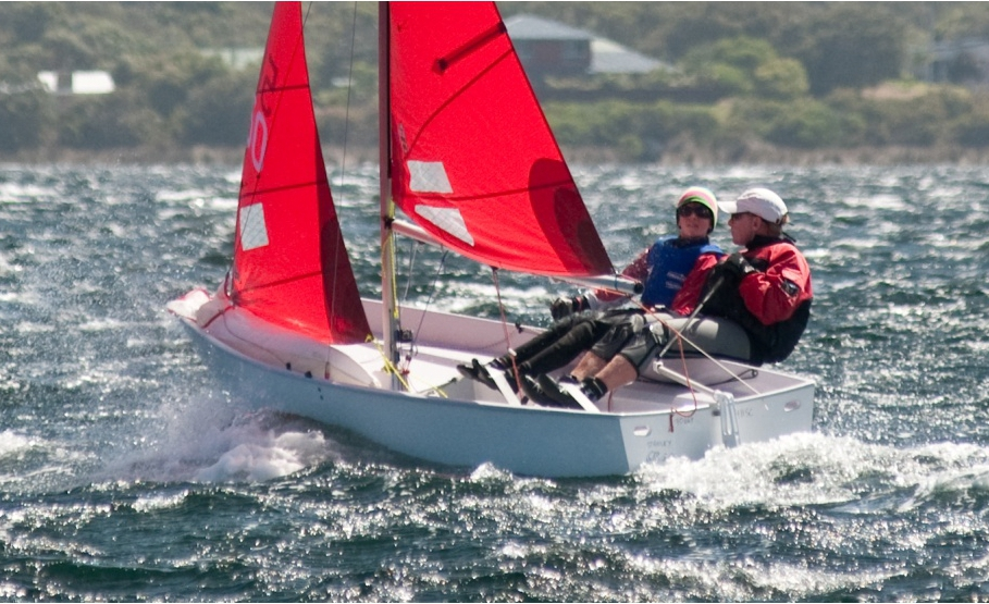A Mirror dinghy being sailed to windward on a very windy day with the helm and crew hiked out and toe straps visible