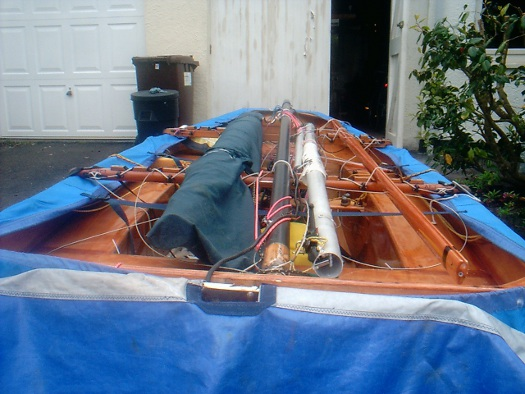 Mirror dinghy on road trailer with spars on carriage beams