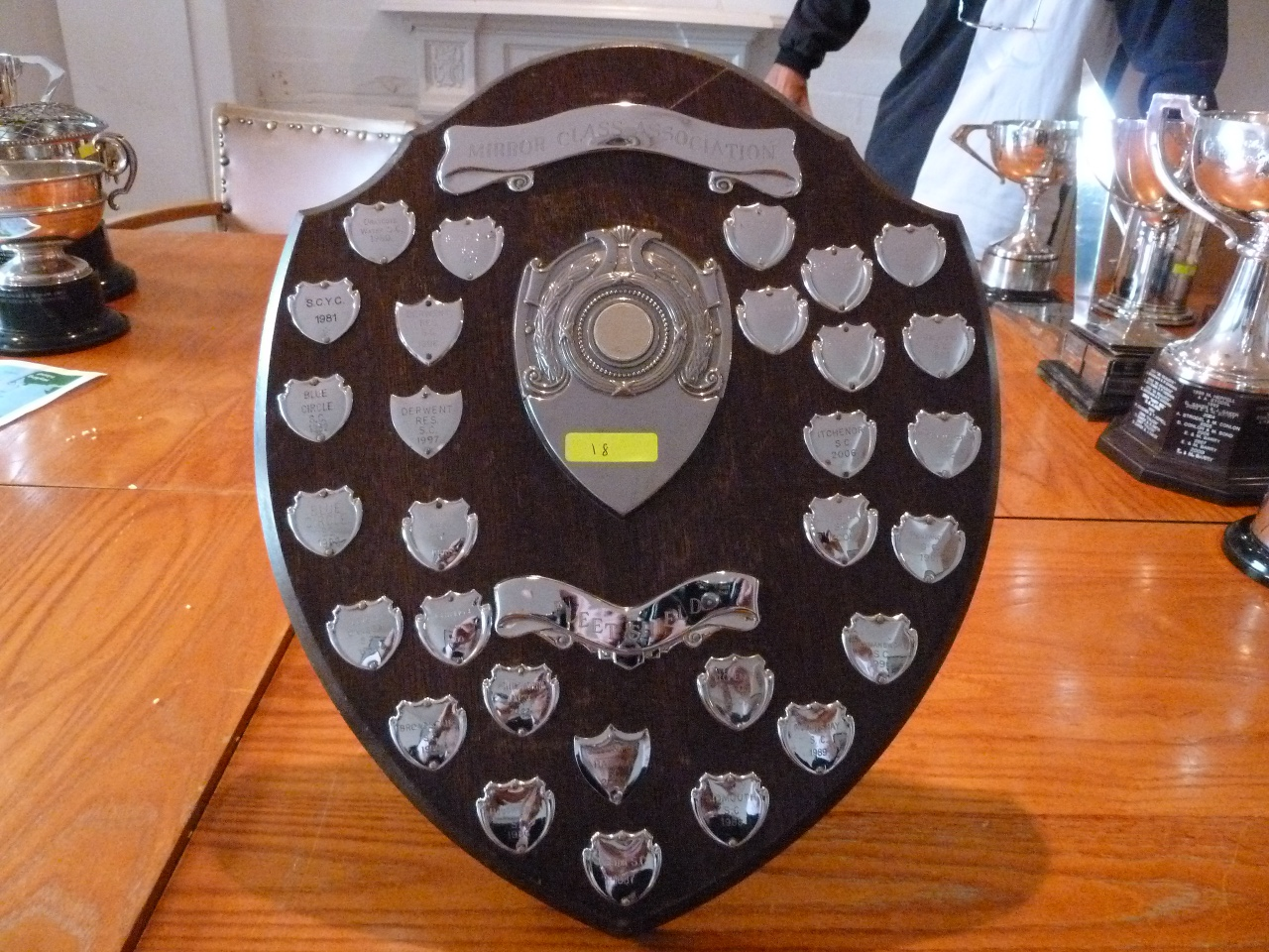 A wooden shield with small engraved shields mounted on it