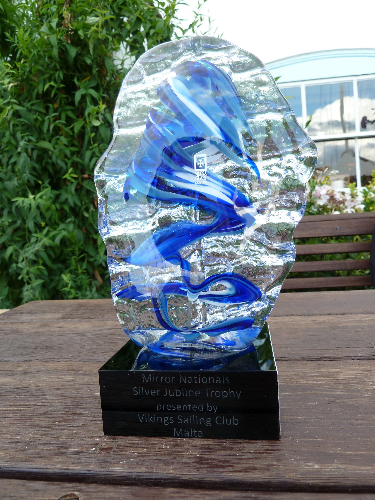A clear and blue glass trophy with a black plastic base