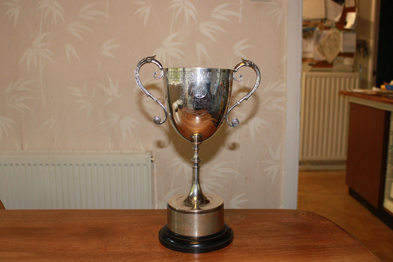 A silver cup with handles and a black plastic base with engraved ring