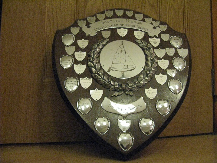 A wooden shield with silver shields mounted on it